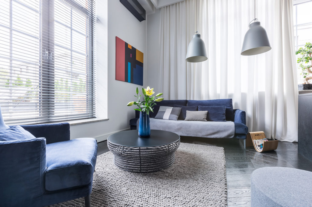 Living room with blue upholstered furniture, window blinds and white net curtain